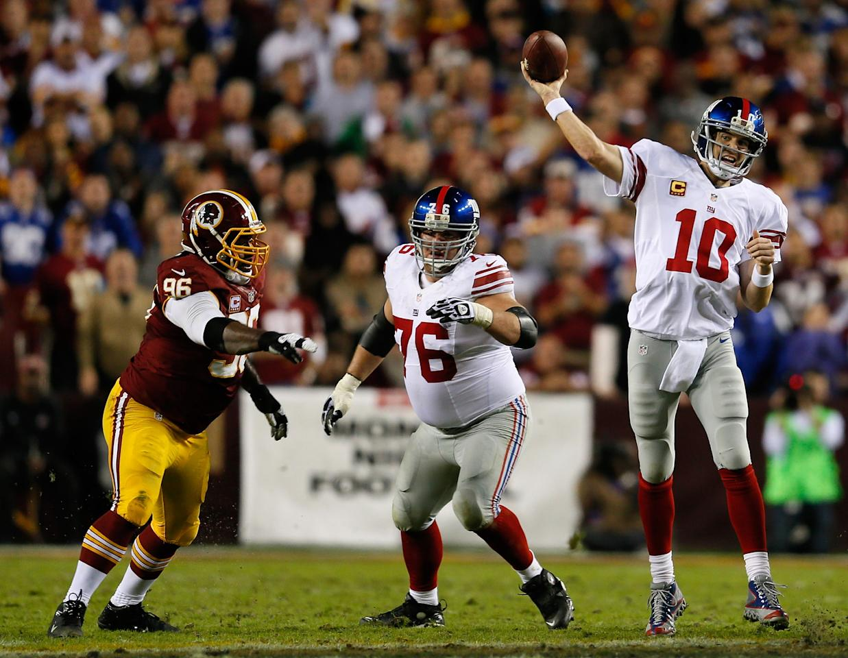 LANDOVER, MD - DECEMBER 03:  Quarterback  Eli Manning #10 of the New York Giants throws the ball as teammate Chris Snee #76 blocks Barry Cofield #96 of the Washington Redskins in the first half at FedExField on December 3, 2012 in Landover, Maryland.  (Photo by Rob Carr/Getty Images)