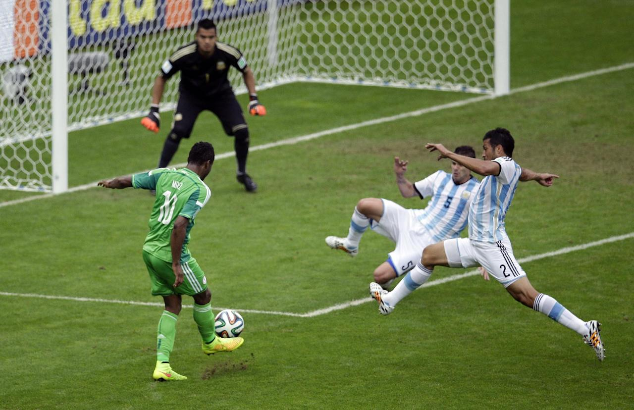Nigeria's Mikel John Obi, left, attempts a shot during the group F World Cup soccer match between Nigeria and Argentina at the Estadio Beira-Rio in Porto Alegre, Brazil, Wednesday, June 25, 2014. (AP Photo/Michael Sohn)