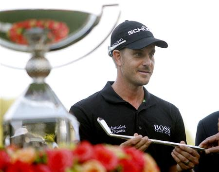 Stenson of Sweden accepts a replica of a Bobby Jones putter as he stands beside the FedExCup trophy after winning the the Tour Championship golf tournament at East Lake Golf Club in Atlanta