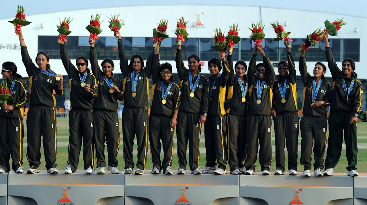 The  Pakistan women's cricket team celebrate on the podium during the medals ceremony of the women's limited overs cricket finals at the 16th Asian Games in Guangzhou on November 19, 2010. Pakistan won gold, Bangladesh won silver and Japan won bronze.  AFP PHOTO / Saeed Khan (Photo credit should read SAEED KHAN/AFP/Getty Images)