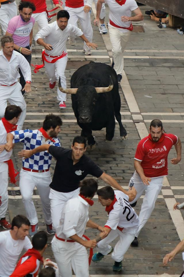 PAMPLONA, SPAIN - JULY 09: Revellers run with a Valdefresno's ranch fighting bull at Calle Estafeta during the fourth day of the San Fermin Running Of The Bulls festival, on July 9, 2013 in Pamplona, Spain. The annual Fiesta de San Fermin, made famous by the 1926 novel of US writer Ernest Hemmingway 'The Sun Also Rises', involves the running of the bulls through the historic heart of Pamplona, this year for nine days from July 6-14. (Photo by Pablo Blazquez Dominguez/Getty Images)