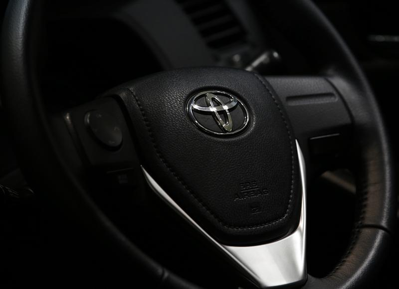 The logo of Toyota Motor Corp. is seen on a steering wheel of the company's car at the Toyota Motor's showroom in Tokyo
