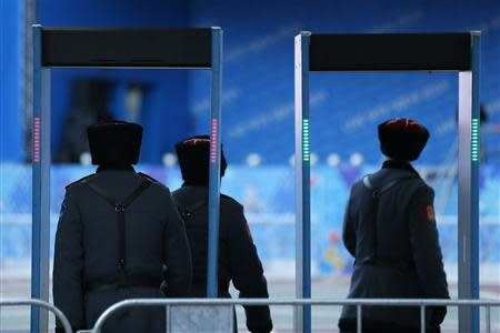 Russian Cossacks enter a security checkpoint as preparations continue for the 2014 Sochi Winter Olympics in Rosa Khutor