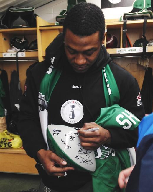 Running back Kory Sheets signs autographs for teammates as the Saskatchewan Roughriders clean out their lockers at Mosaic Stadium in Regina on Tuesday, November 26, 2013. The Riders won the Grey Cup Sunday over the Hamilton Tiger-Cats. THE CANADIAN PRESS/Jennifer Graham