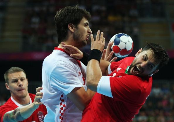 LONDON, ENGLAND - AUGUST 12:  Marko Kopljar (center) #8 of Croatia and Attila Vadkerti #24 of Hungary collide during the Men's Handball Bronze Medal Match on Day 16 of the London 2012 Olympic Games at Basketball Arena on August 12, 2012 in London, England.  (Photo by Jeff Gross/Getty Images)