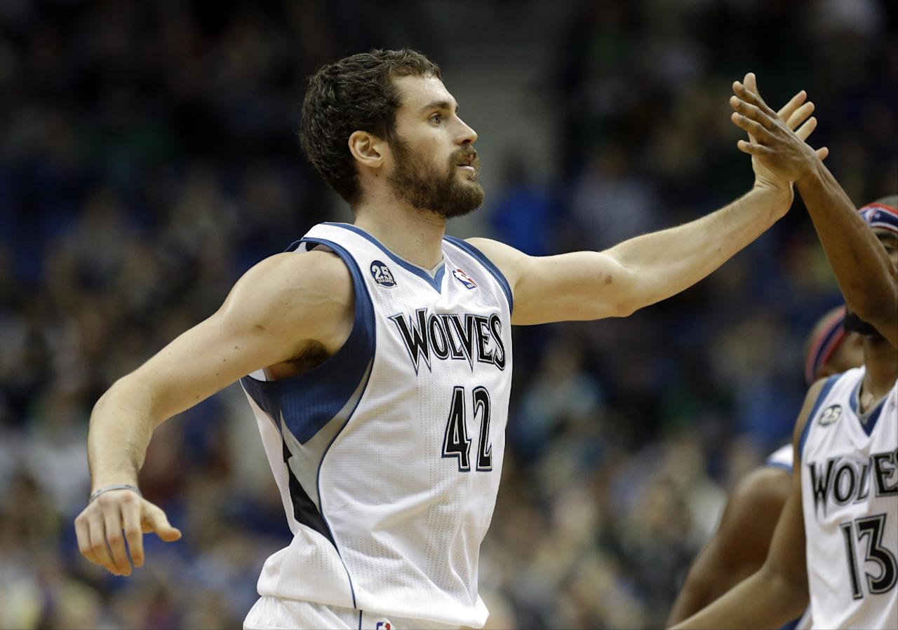 Minnesota Timberwolves' Kevin Love, left, is congratulated by Corey Brewer after a basket in the second half of an NBA basketball game against the Dallas Mavericks, Friday, Nov. 8, 2013, in Minneapolis. The Timberwolves won 116-108. (AP Photo/Jim Mone)