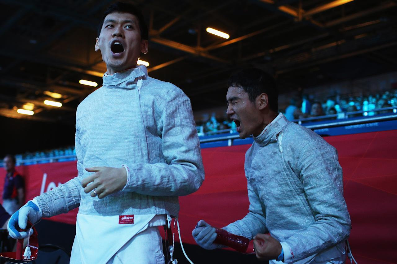 LONDON, ENGLAND - AUGUST 03:  Bongil Gu and Junghwan Kim of Korea celebrate beating Italy during the Men's Sabre Team Fencing semifinal on Day 7 of the London 2012 Olympic Games at ExCeL on August 3, 2012 in London, England.  (Photo by Hannah Johnston/Getty Images)