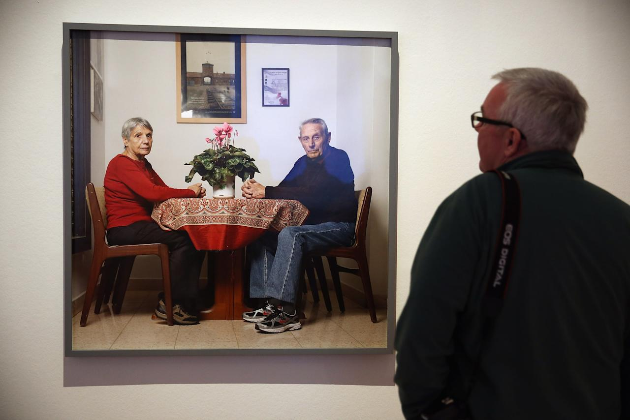 """BERLIN, GERMANY - APRIL 04:  A visitor looks at a photograph of Jews Herbert and Rina Nussan sitting at their kitchen table at the exhibition """"The Whole Truth - Everything You Always Wanted To Know About Jews . . . """" at the Juedisches Museum (Jewish Museum) on April 4, 2013 in Berlin, Germany. The exhibition presents every-day aspects of Jewish life, poses simple questions answered with exhibits and challenges certain stereotypes. However its live exhibit, which features a Jewish person who sits in a plastic enclosure open on one side for several hours a day to answer visitors' questions, has sparked criticism from some Jewish groups.  (Photo by Sean Gallup/Getty Images)"""