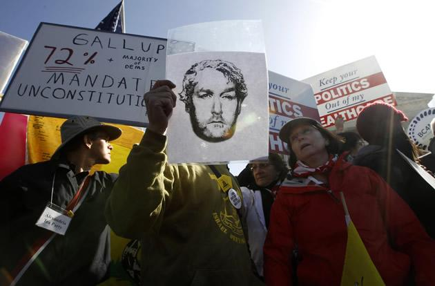 An image of the late conservative media publisher and activist Andrew Breitbart is held up as opponents of health care reform rally in front of the Supreme Court.