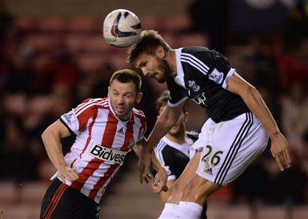 Sunderland's Bardsley challenges Southampton's Hooiveld during their English League Cup fourth round soccer match at the Stadium of Light in Sunderland