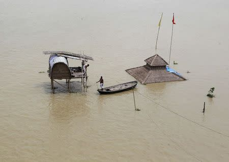 A sadhu stands on a boat near a submerged hut on the flooded banks of river Ganga after heavy monsoon rains in Allahabad