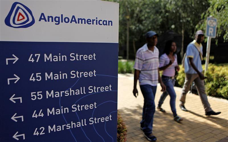 People walk past a board outside the Anglo American offices in Johannesburg