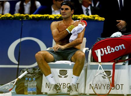 Switzerland's Federer changes his jersey during his match against Mannarino of France at the Swiss Indoors ATP tennis tournament in Basel