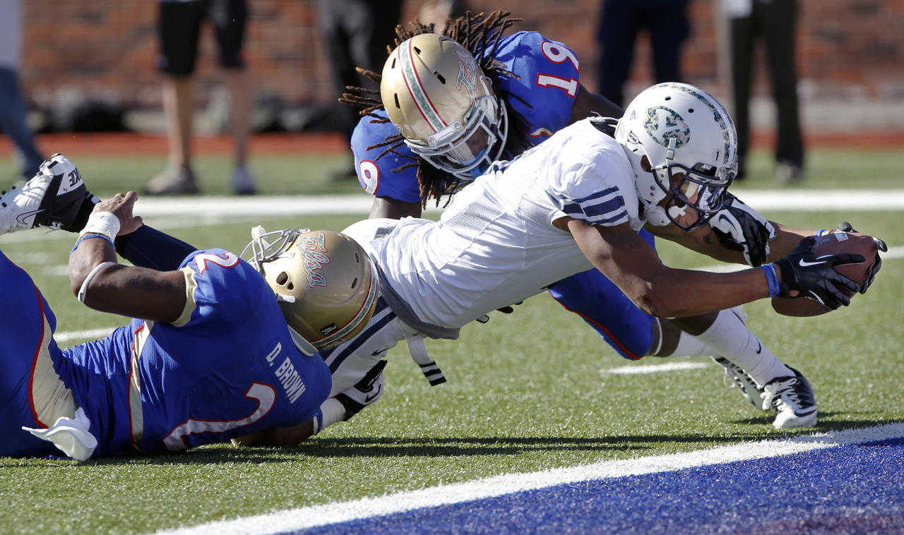BYU wide receiver Cody Hoffman (2) stretches out to score a touchdown in front of Tulsa linebacker DeAundre Brown (2) and defensive back Milton Howell (19) during the second quarter of the Armed Forces Bowl NCAA college football game on Friday, Dec. 30, 2011, in Dallas. (AP Photo/John F. Rhodes)