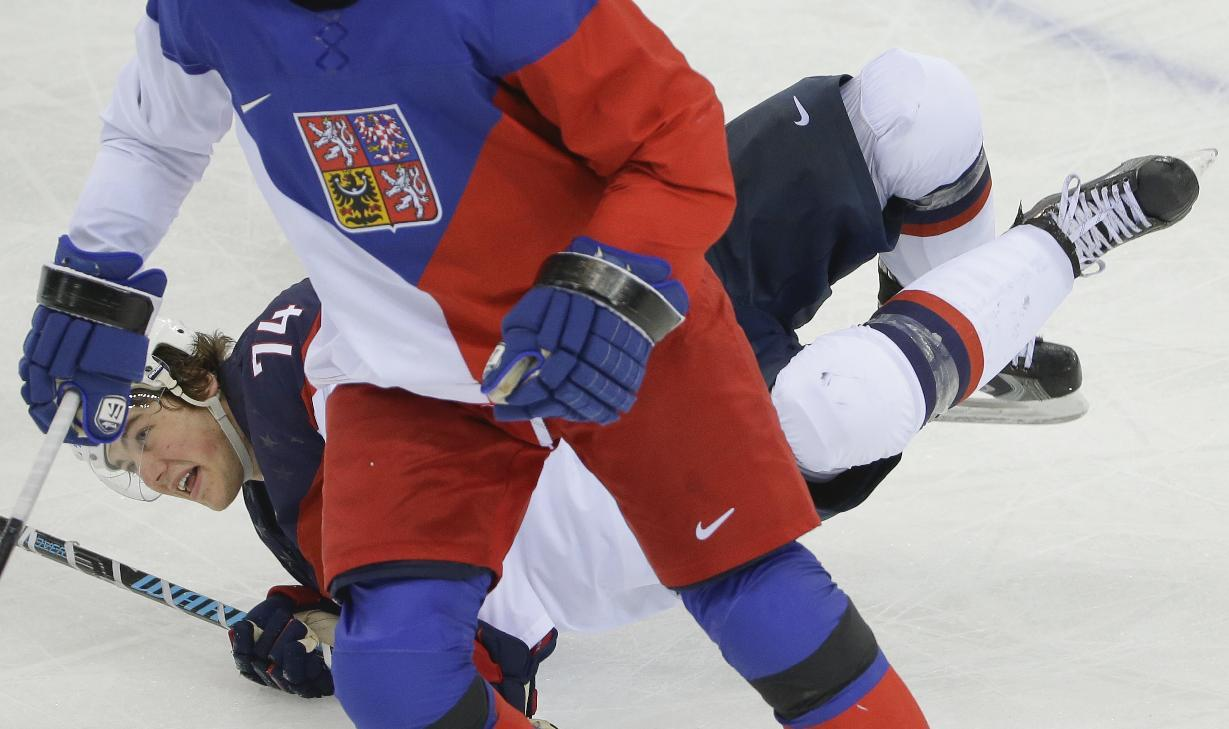 USA forward T.J. Oshie looks up form the ice after falling while attaching Czech Republic defenseman Tomas Kaberle during the third period of men's quarterfinal hockey game in Shayba Arena at the 2014 Winter Olympics, Wednesday, Feb. 19, 2014, in Sochi, Russia. (AP Photo/Matt Slocum)