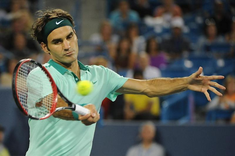 Roger Federer of Switzerland returns the ball to Milos Raonic of Canada during a match on day 8 of the Western & Southern Open at the Linder Family Tennis Center on August 16, 2014 in Cincinnati, Ohio