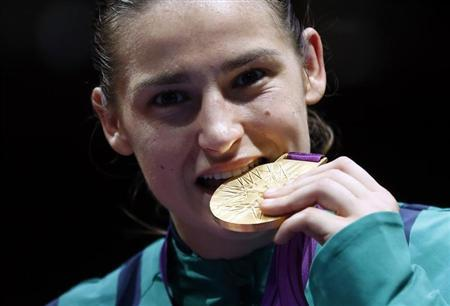 Taylor bites her gold medal following the presentation ceremony for the Women's Light (60kg) boxing competition at the London Olympic Games