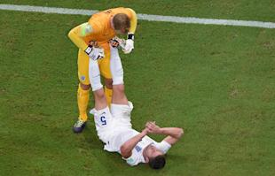 England's goalkeeper Joe Hart, left, stretches the calf muscles of his teammate Gary Cahill during their game against Italy. (AP)