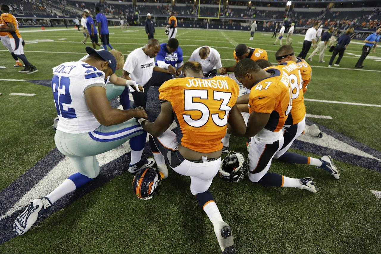 Members of the Dallas Cowboys and the Denver Broncos share a moment following a NFL preseason football game, Thursday, Aug. 28. 2014, in Arlington, Texas. (AP Photo/LM Otero)