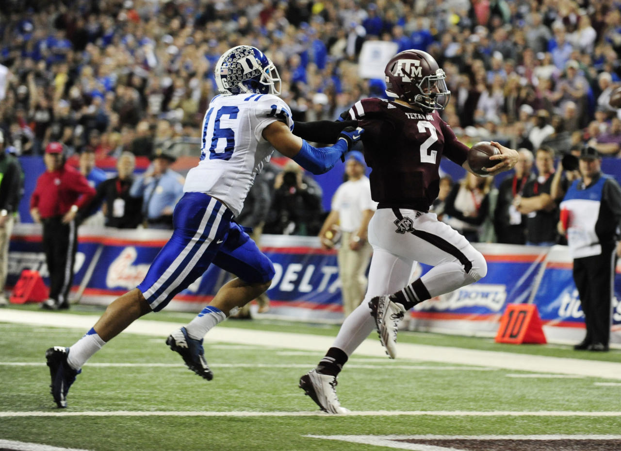 Dec 31, 2013; Atlanta, GA, USA; Texas A&M Aggies quarterback Johnny Manziel (2) runs a touchdown past the defense of Duke Blue Devils safety Jeremy Cash (16) in the 2013 Chick-fil-A Bowl at the Georgia Dome. (Kevin Liles-USA TODAY Sports)