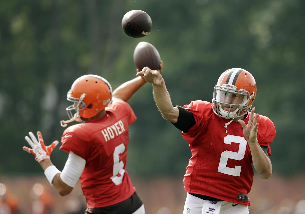 Cleveland Browns quarterbacks Johnny Manziel (2) and Brian Hoyer pass during practice at NFL football training camp in Berea, Ohio Tuesday, Aug. 12, 2014. (AP Photo/Mark Duncan)
