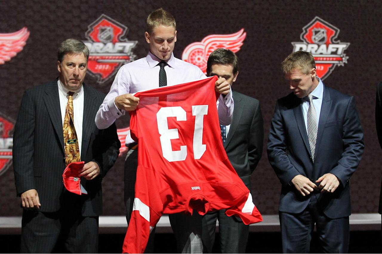 Jun 30, 2013; Newark, NJ, USA; Anthony Mantha puts on a team jersey after being introduced as the number twenty overall pick to the Detroit Red Wings during the 2013 NHL Draft at the Prudential Center. (Ed Mulholland-USA TODAY Sports)