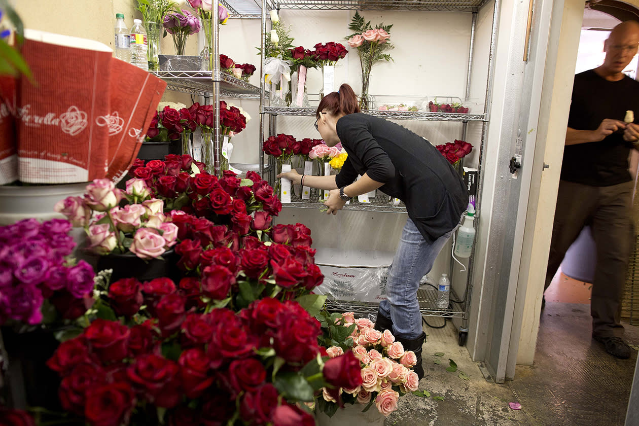 Preparing for a full day of weddings on 12-12-12, Nic Simpson, left, checks bouquets in a cooler at the Viva Las Vegas Wedding Chapel in Las Vegas.