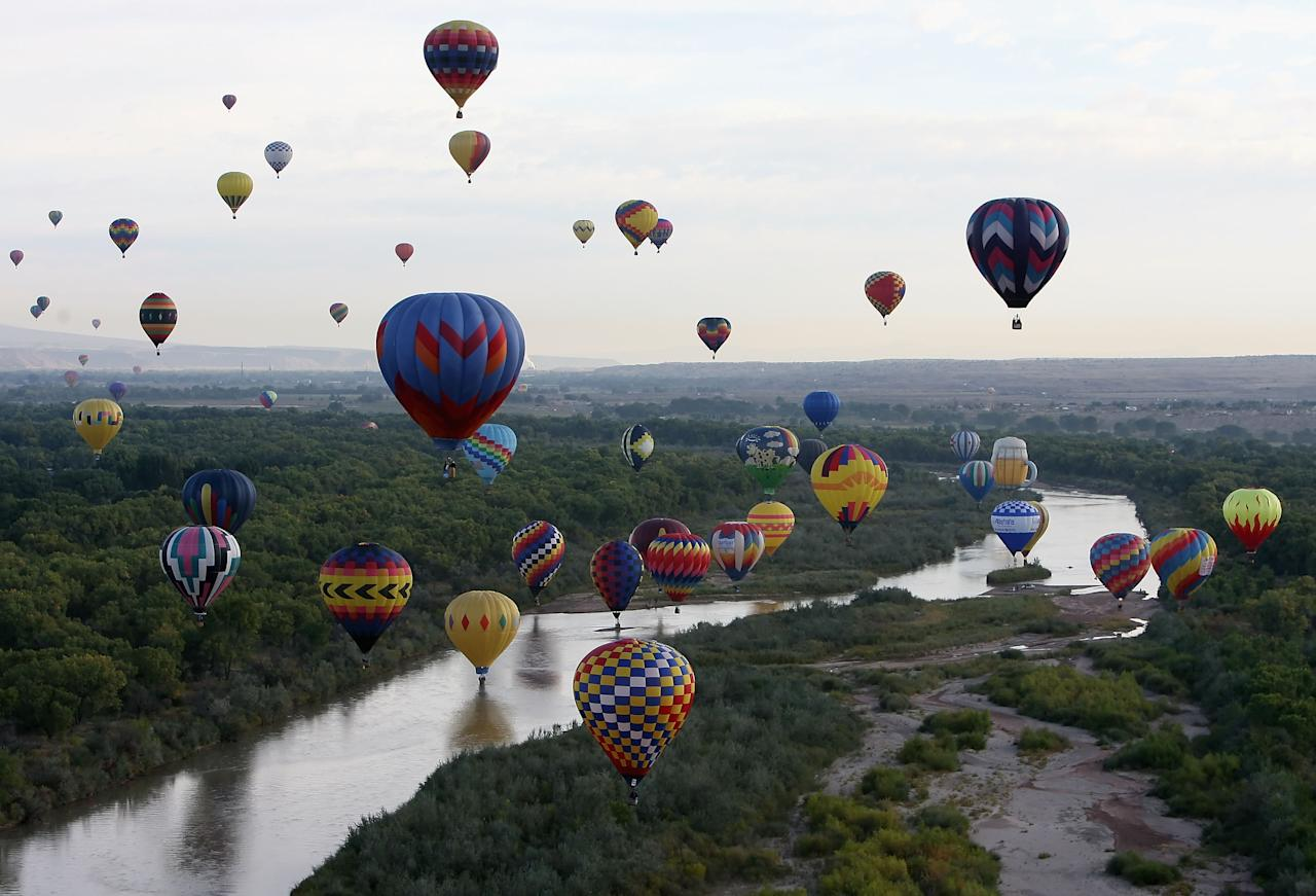 Hot air balloons soar over the Rio Grande during the Albuquerque International Balloon Fiesta on October 4, 2008 in Albuquerque, New Mexico.  This year there are over 600 hot air balloons, representing 42 states and 24 countries.  (Photo by Christian Petersen/Getty Images)