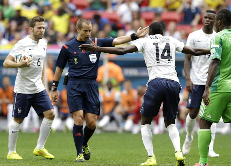 Referee Mark Geiger from the U.S marks a fail to France's Blaise Matuidi (14) during the World Cup round of 16 soccer match between France and Nigeria at the Estadio Nacional in Brasilia, Brazil, Monday, June 30, 2014. At left is France's Yohan Cabaye