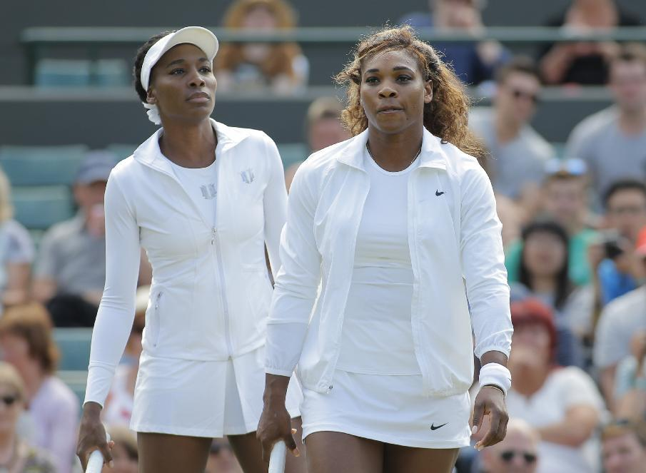 Serena Williams of U.S, right, and her sister Venus Williams walk onto the court to warm up for their women's doubles match against Kristina Barrois of Germany and Stefanie Voegele of Switzerland at the All England Lawn Tennis Championships in Wimbledon, London, Tuesday July 1, 2014. (AP Photo/Pavel Golovkin)