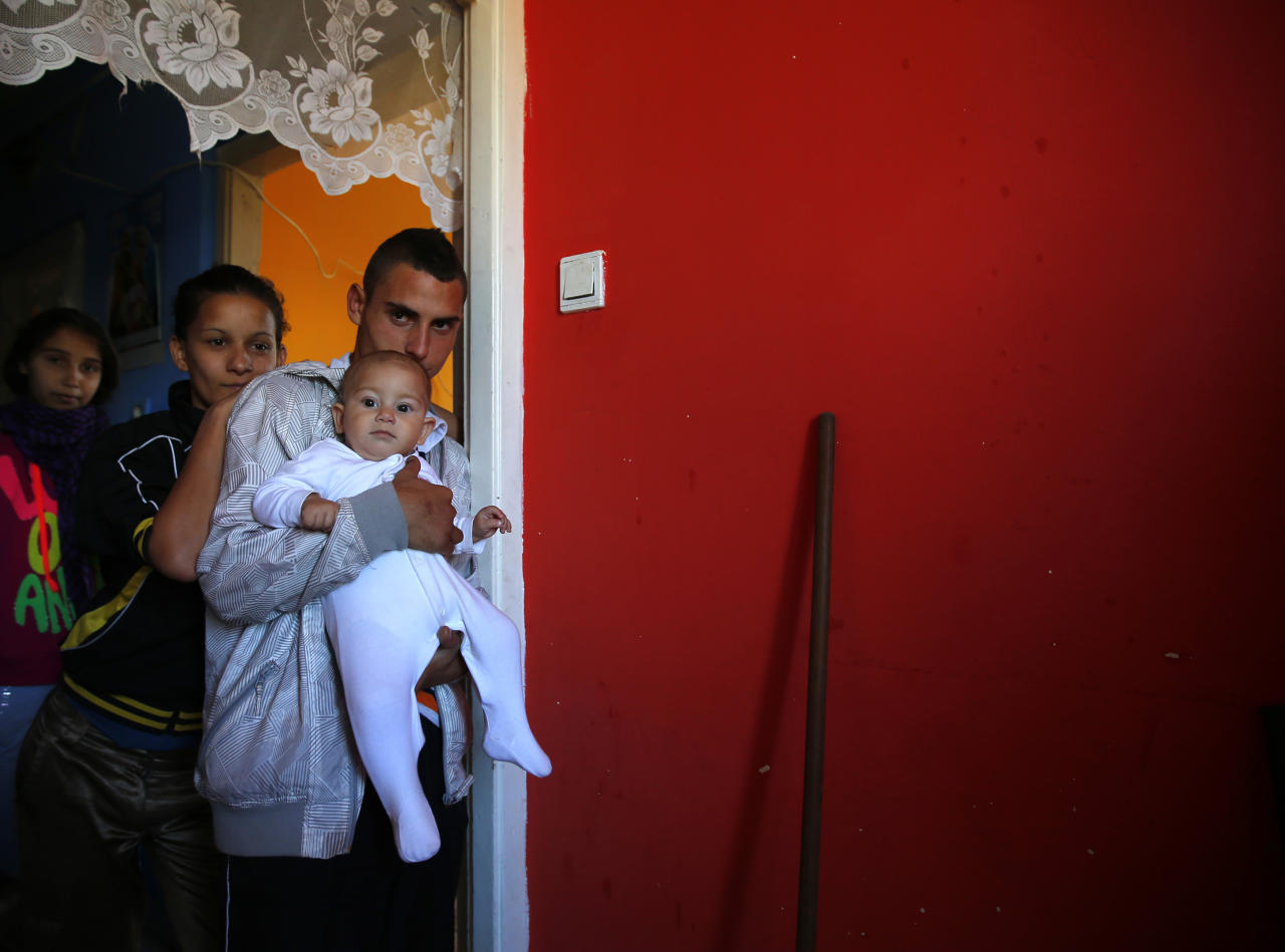 A Roma family stands in their apartment at the Avas apartment block in Miskolc, 180 km (112 miles) east of Budapest October 17, 2012. Spurred by desperate poverty in the nearby countryside, hundreds of destitute Romas moved into local apartment blocks in the last decade. Their presence has caused widespread friction with earlier tenants most of whom are not Roma. Complaining about what they say is a grave deterioration of public safety and insufficient government action to tackle it, the far right Jobbik party announced a big protest march on Wednesday. REUTERS/Laszlo Balogh (HUNGARY - Tags: POLITICS SOCIETY)