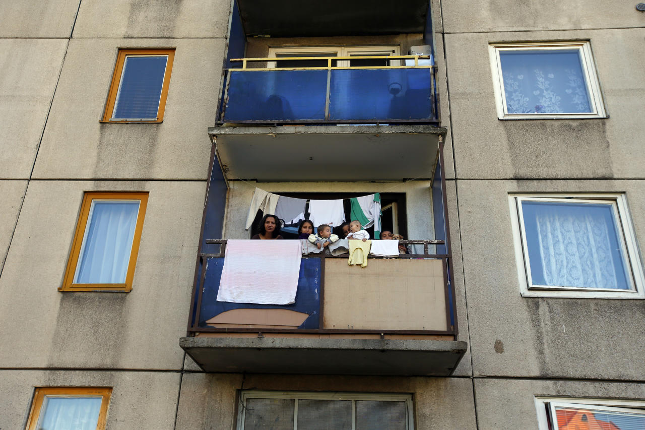 A Roma family gathers at the balcony of their apartment at the Avas apartment projects in Miskolc, 180 km (112 miles) east of Budapest, October 17, 2012. The city's ex-communist Avas housing projects, home to about 40,000 people, have seen mass immigration of destitute Roma from the countryside, where living conditions are often rustic. Long-time residents have shunned the new Roma occupants, many of whom have large families crammed into tiny flats. Picture taken October 17. To match story HUNGARY-FARRIGHT/  REUTERS/Laszlo Balogh (HUNGARY - Tags: POLITICS CIVIL UNREST REAL ESTATE BUSINESS SOCIETY IMMIGRATION)