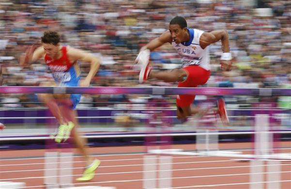 Cuba's Orlando Ortega clears a hurdle in his men's 110m hurdles round 1 heat during the London 2012 Olympic Games at the Olympic Stadium August 7, 2012.
