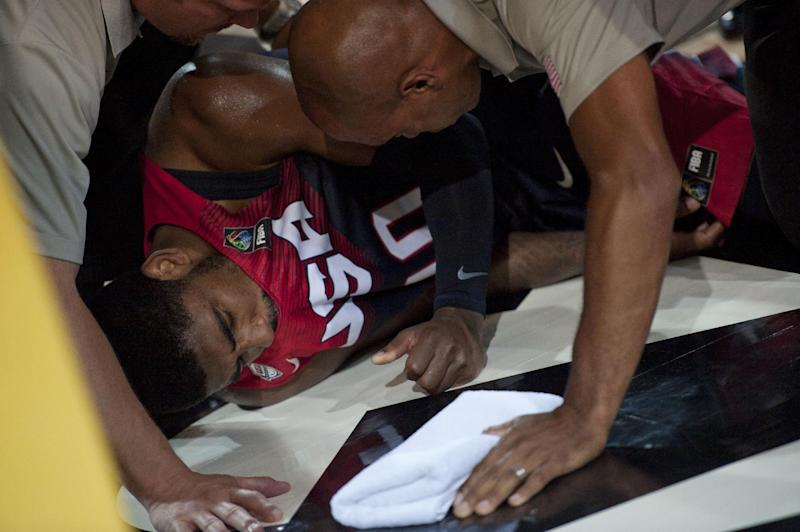 Kyrie Irving of the US, is attended to on the court after falling, during the Group C Basketball World Cup match against Ukraine, in Bilbao northern Spain, Thursday, Sept. 4, 2014. The 2014 Basketball World Cup competition take place in various cities in Spain from Aug. 30 through to Sept. 14