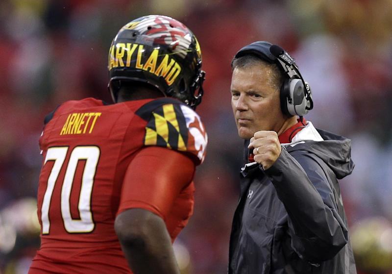 In this Sept. 21, 2013 file photo, Maryland head coach Randy Edsall, right, fist-bumps offensive linesman De'Onte Arnett who jogs off the field in the first half of an NCAA college football game against West Virginia,  in Baltimore. Maryland begins Big Ten play this season with a schedule that includes Ohio State, Michigan, Wisconsin and Michigan State