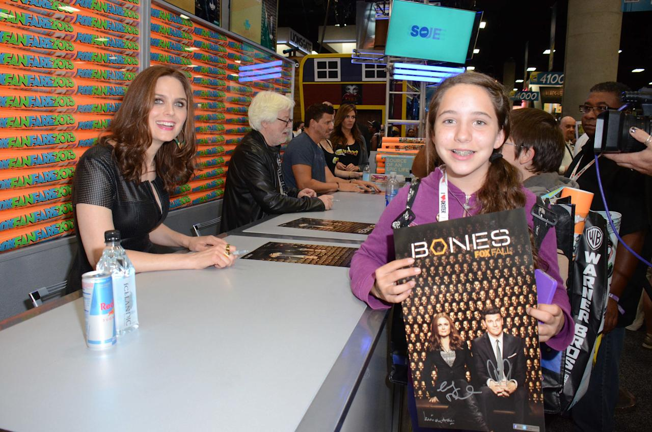 """Emily Deschanel greets and signs an exclusive limited edition """"Bones"""" poster for fans on Friday, July 19 during Fox Fanfare at San Diego Comic-Con 2013."""