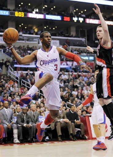Los Angeles Clippers guard Chris Paul, left, passes the ball as Portland Trail Blazers forward Luke Babbitt defends during the first half of their NBA basketball game, Friday, March 30, 2012, in Los Angeles. (AP Photo/Mark J. Terrill)