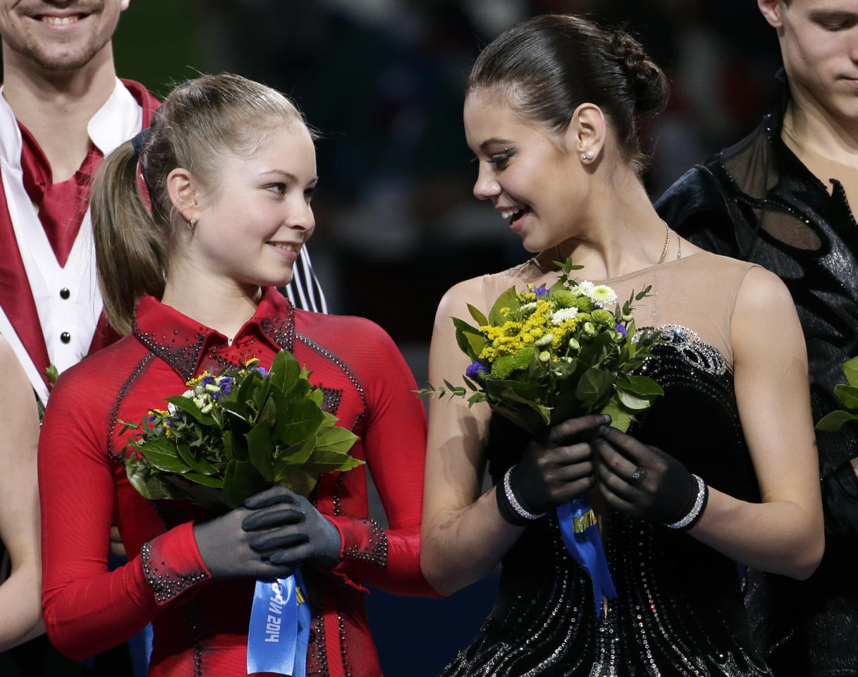 Elena Ilinykh, right, speaks with Julia Lipnitskaia as they stand on the podium during the flower ceremony after Russia placed first in the team figure skating competition at the Iceberg Skating Palace during the 2014 Winter Olympics, Sunday, Feb. 9, 2014, in Sochi, Russia. (AP Photo/Bernat Armangue)
