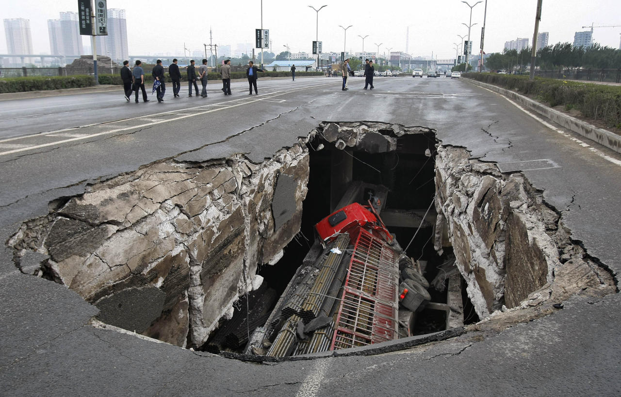 A truck is seen in a hole after part of the structure of a bridge collapsed into a river in Changchun, Jilin province May 29, 2011. Two truck passengers were injured, while the cause of the accident is still under investigation, local media reported. Picture taken May 29, 2011. REUTERS/China Daily (CHINA - Tags: TRANSPORT DISASTER SOCIETY IMAGES OF THE DAY) CHINA OUT. NO COMMERCIAL OR EDITORIAL SALES IN CHINA - RTR2N2NC