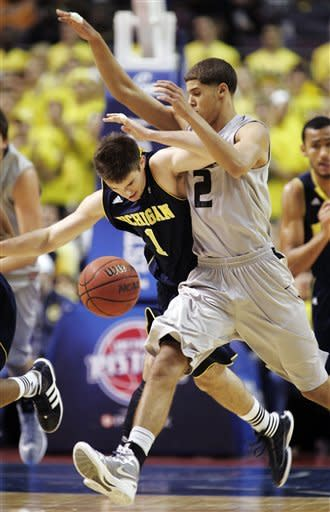 Oakland forward Dante Williams (2) collides with Michigan guard Stu Douglass (1) while chasing a loose ball in the first half of an NCAA college basketball game, Saturday, Dec. 10, 2011, in Auburn Hills, Mich. (AP Photo/Duane Burleson)