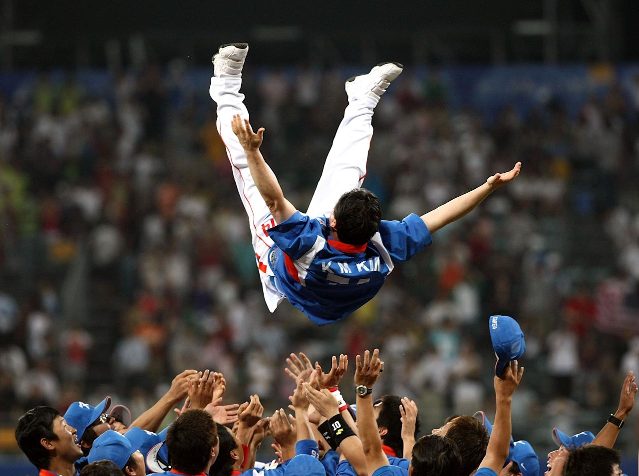 BEIJING - AUGUST 23:  Manager Kim Kyungmoon #74 of Korea is tossed in the air by his players after Korea won 3-2 against Cuba during the men's gold medal baseball game held at Wukesong Baseball Field on Day 15 of the Beijing 2008 Olympic Games on August 23, 2008 in Beijing, China.  (Photo by Jonathan Ferrey/Getty Images)