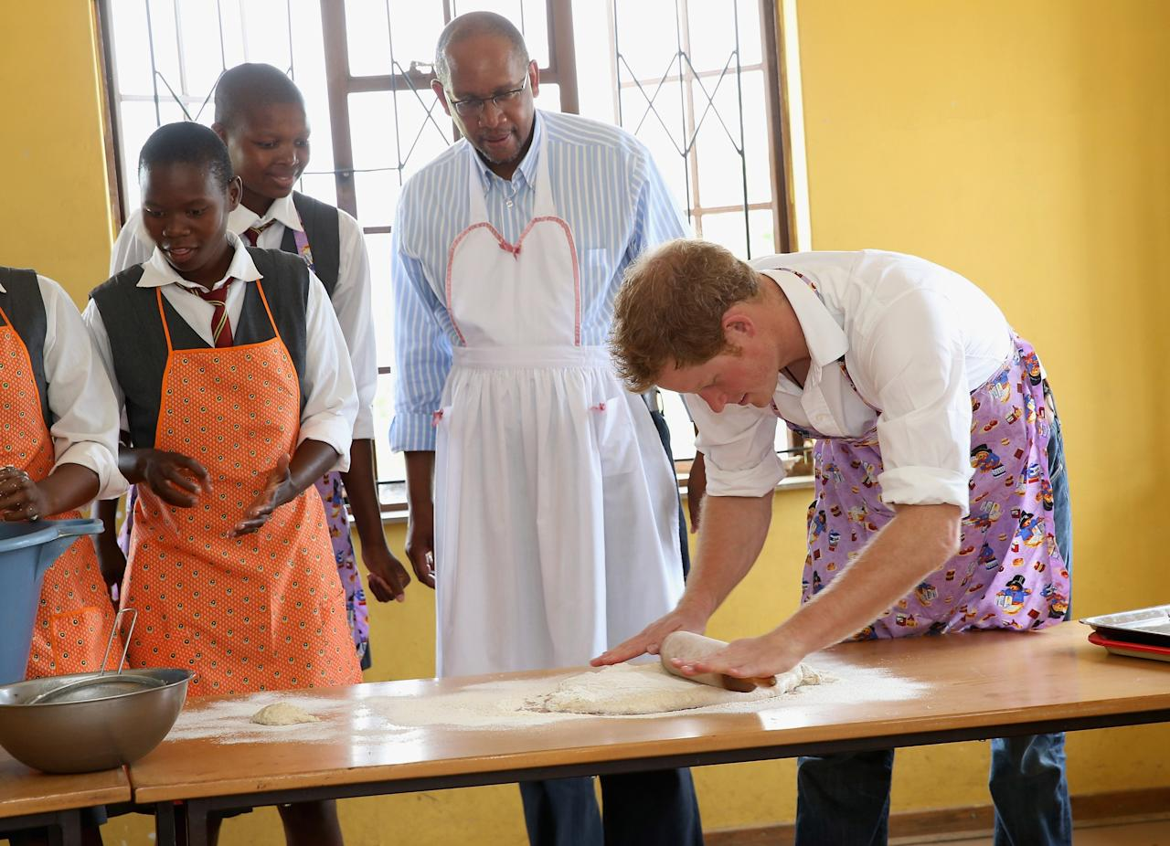 MASERU, LESOTHO - FEBRUARY 27:  Prince Harry does some baking during his visit to Kananelo Centre for the deaf, a project supported by his charity Sentebale on February 27, 2013 in Maseru, Lesotho. Sentebale is a charity founded by Prince Harry and Prince Seeiso of Lesotho. It helps the most vulnerable children in Lesotho get the support they need to lead healthy and productive lives. Sentebale works with local grassroots organisations to help these children, the victims of extreme poverty and Lesotho's HIV/AIDS epidemic. Cathy Ferrier was appointed as Sentebale's Chief Executive in March 2012 and is spearheading a fundraising initiative to build the Mamohato Centre which will provide psychosocial support for children and young people infected with HIV. Prince Harry is due to pay a visit to Lesotho this week to catch up on his charity's progress and meet key children who will be supported by the charity.  (Photo by Chris Jackson/Getty Images)