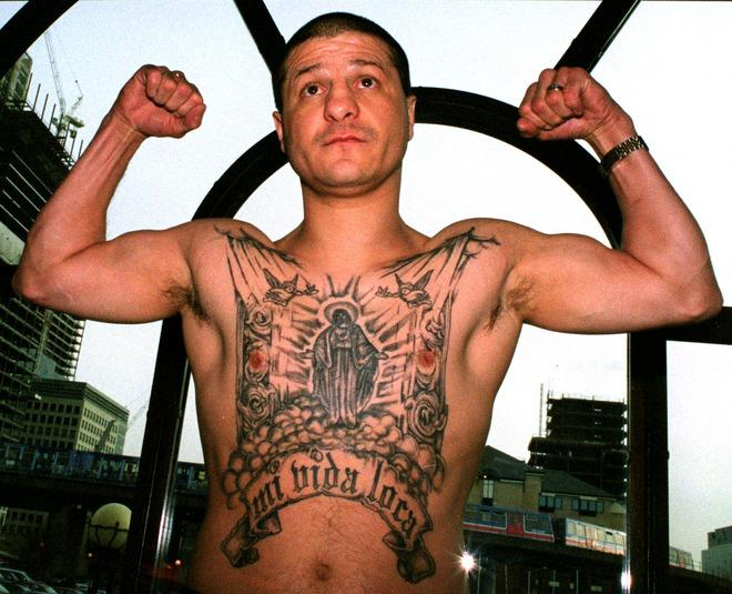 """LONDON, UNITED KINGDOM - JANUARY 15 2002:  Jonny Tapia of Albuquerque, USA shows off his tatoo's at a Press Conference before his fight against Eduardo Alvarez of Argentina held at the International Hotel in the Docklands, London.  Johnny Tapia has been found dead at his home in Albuquerque, New Mexico at the age of 45. Police reports have stated that the death """"did not appear to be suspicious"""".  (Photo by Warren Little/Getty Images)"""