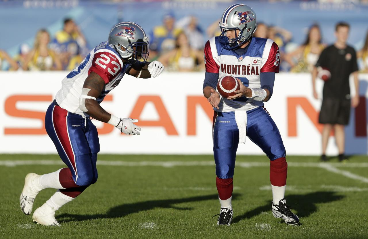 Montreal Alouettes quarterback Josh Neiswander (R) hands off the football to running back Jerome Messam during the first half of the 2013 CFL Touchdown Atlantic game against the Hamilton Tiger-Cats in Moncton, New Brunchwick, September 21, 2013. 