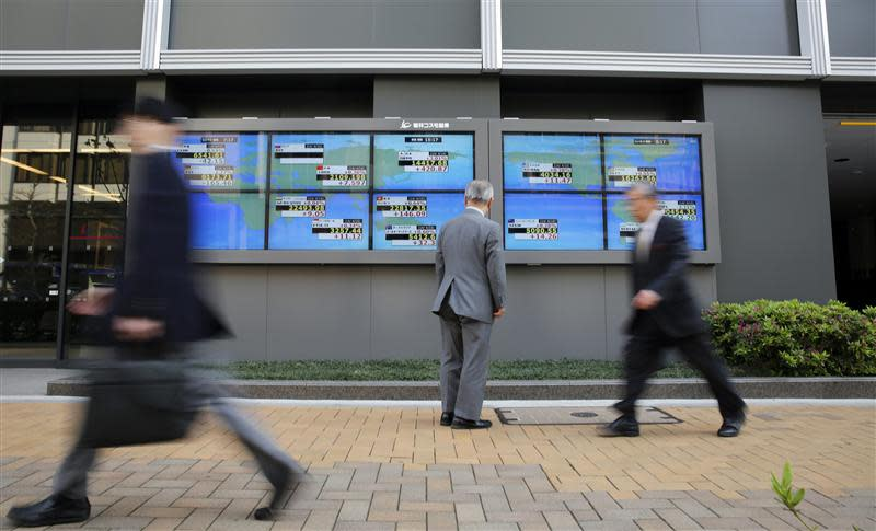 Man looks at an electronic board displaying Japan's Nikkei average and various countries' stock indices outside a brokerage in Tokyo