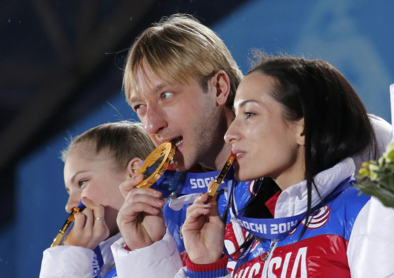 Yulia Lipnitskaya (L), Evgeny Plyushchenko (C) and Ksenia Stolbova of the gold medal-winning Russian figure skating team bite into their medals, during the medal ceremony for the figure skating team ice dance free dance at the Sochi 2014 Winter Olympics February 10, 2014. REUTERS/David Gray (RUSSIA - Tags: OLYMPICS SPORT FIGURE SKATING)