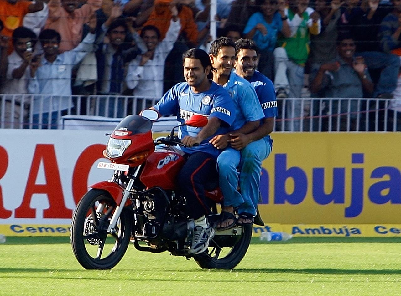 Indian cricketers Mahendra Singh Dhoni, (L) Irfan Pathan (C) and Robin Uthappa drive around the stadium on a motorbike after the fourth One Day International (ODI) match against the West Indies in Vadodara, 31 January 2007. India won the four match ODI series by 3-1.  AFP PHOTO/ Indranil MUKHERJEE