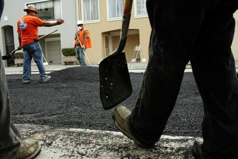 Workers spread asphalt on a street in the Cow Hollow neighborhood in San Francisco, California