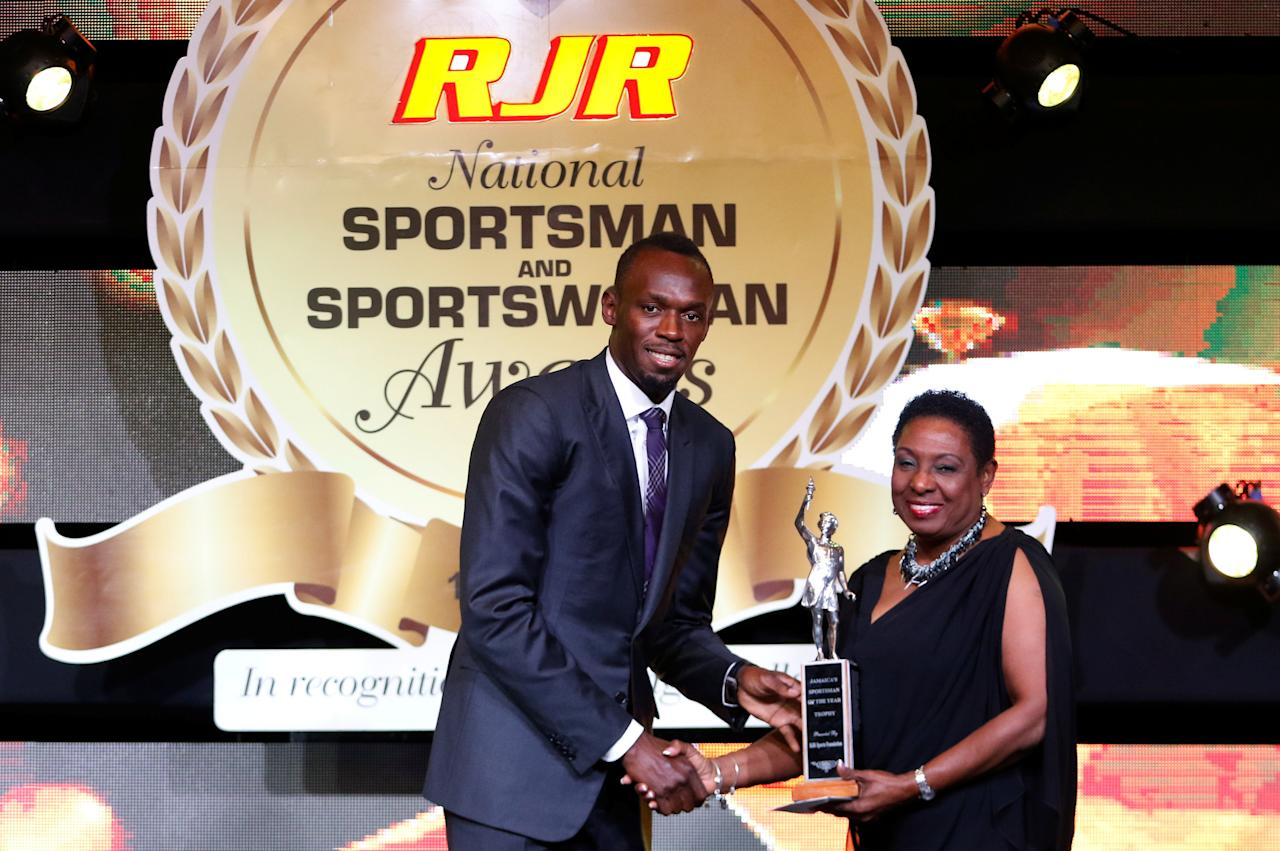 Jamaican sprinter Usain Bolt is being presented with the Sportsman of the Year 2016 award by Minister of Information, Youth, Sports and Culture Olivia Grange during the National Sportsman and Sportswoman of the Year award ceremony in Kingston, Jamaica January 13, 2017. Picture taken January 13, 2017. REUTERS/Gilbert Bellamy