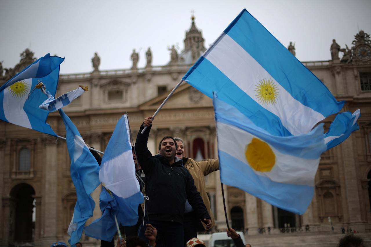 VATICAN CITY, VATICAN - MARCH 17:  Men wave the flag of Argentina in St Peter's Square after Pope Francis gave his first Angelus blessing on March 17, 2013 in Vatican City, Vatican. The Vatican is preparing for the inauguration of Pope Francis on March 19, 2013 in St Peter's Square.  (Photo by Peter Macdiarmid/Getty Images)